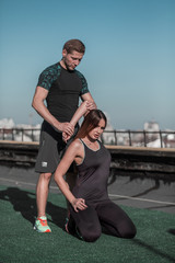 Fitness on the roof, young woman stretching with personal trainer. Sportive lifestyle, pretty young female stertching after workout.