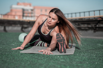 Fitness on the roof, sporty woman stretching. Young female with long hair, training on the roof of the building in the city.