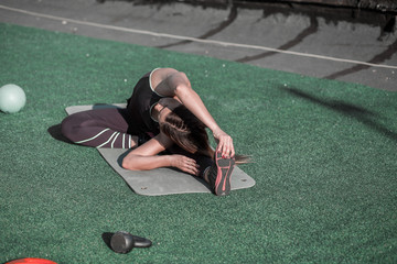 Sporty woman stretching on the roof after workout. Sportive lifestyle, female finishing traning with stretching.
