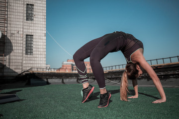 Gymnast woman training on the rooftop. Flexible sporty girl training in the sun.