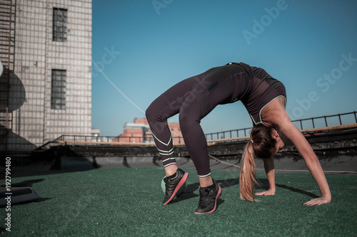 e08bca3b5522 Gymnast woman training on the rooftop. Flexible sporty girl training in the  sun.
