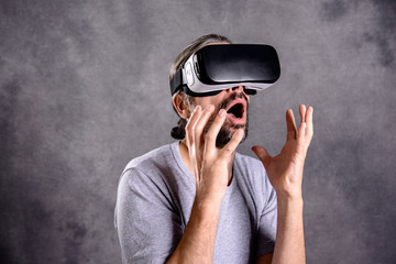 man with virtual reality glasses pointing looking surprised