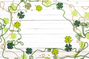 Frame of felt four-leaf clover and beads on white wooden background. Space for text.