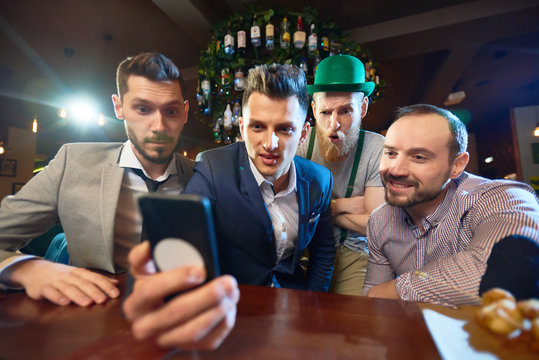 Group of friends gathered together in modern pub and watching funny video on smartphone while celebrating St. Patricks Day, bearded man wearing leprechaun costume