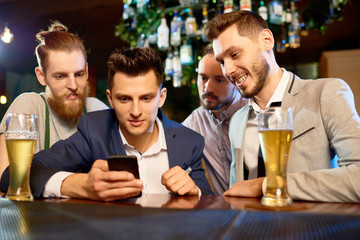 Group of bearded colleagues gathered together in pub after hard working day, drinking beer and watching video on smartphone