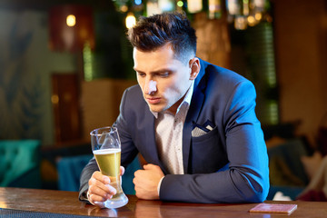 Waist-up portrait of handsome young businessman sitting at bar counter with beer glass in hand while taking rest after hard working day, blurred background
