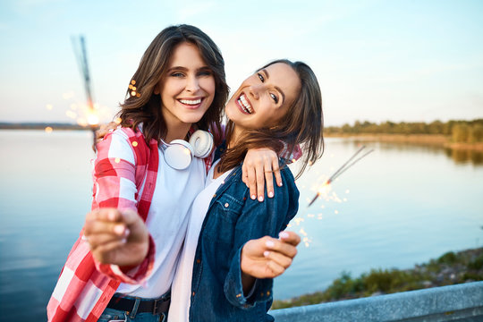 Two beautiful young women smiling and staring at camera holding sparklers with view of lake in background