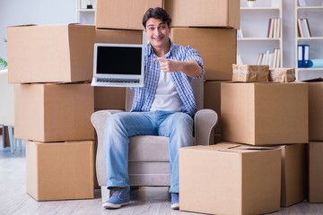Young man moving in to new house with boxes