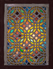 Perforated stucco window decorated with colorful stain glass with geometrical circular patterns, one of the traditions of the Ottoman era
