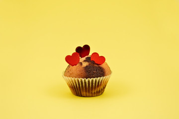 Muffin with hearts stock images. Chocolate muffin with heart on a yellow background. Sweet birthday pastry. Valentines Day concept