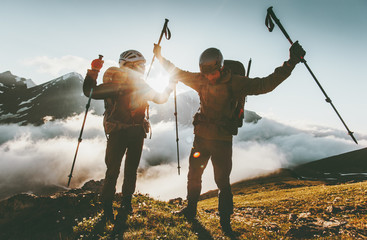 Happy travel couple man and woman on mountain summit love and adventure hiking Lifestyle wanderlust concept sunset light.