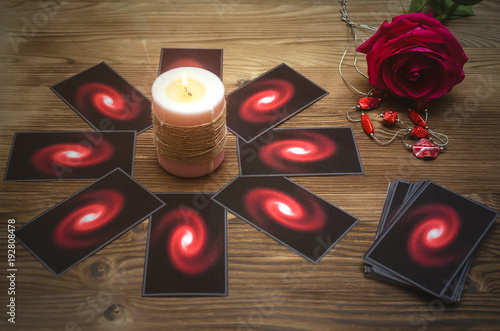 Tarot cards and rose flower on fortune teller desk table background