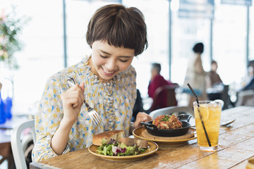 Deurstickers Kruidenierswinkel カフェでランチを食べる女性