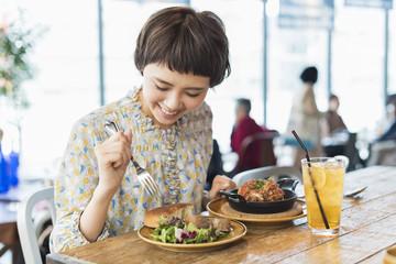 Fotorolgordijn Kruidenierswinkel カフェでランチを食べる女性