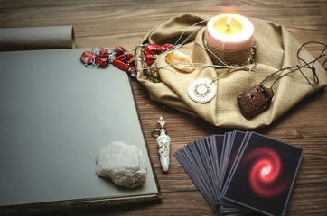 Tarot cards deck and open book of magic with copy space on fortune teller desk table bakground. Future reading concept.