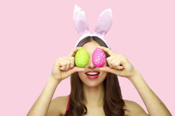 Studio shot of a happy young woman wearing bunny ears and holding up a colorful Easter eggs in front of her eyes isolated on pink background