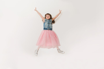Funny kid in dress jumping and laughing on  background.