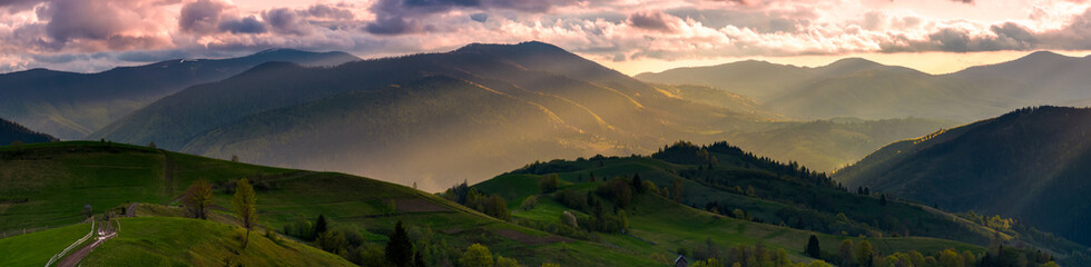 gorgeous panorama of countryside at sunset in springtime. landscape with rural fields on rolling hills and mountain ridge in sunlight in the distance