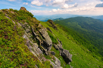 grassy slopes of mountain ridge with rocky cliffs. beautiful summer landscape under the cloudy sky