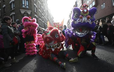 Spectators watch performers dressed in traditional lion and dragon costumes take part in the Chinese New Year parade through central London