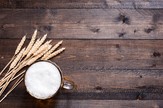 Wooden background with beer mug and wheat ears