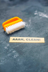 Cleaning house or office concept. Yellow cleaning brush, AAAH, CLEAN inscription on a dark concrete background. Top view, closeup
