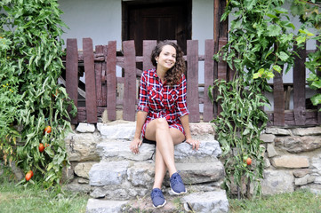 young girl sitting on the steps of an old rural house.