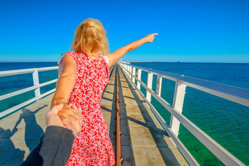 Follow me, blonde woman holding hands at Busselton jetty in Busselton, Western Australia. Concept of the journey of woman tourist traveler, holding man by hand over iconic wooden pier in WA, Australia
