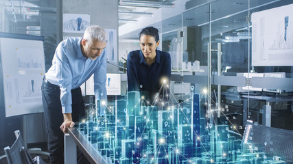 Male and Female Architects Work with Holographic Augmented Reality 3D City Model. Technologically Advanced Office Professional People Use Virtual Reality Modeling Software Application. Wall mural