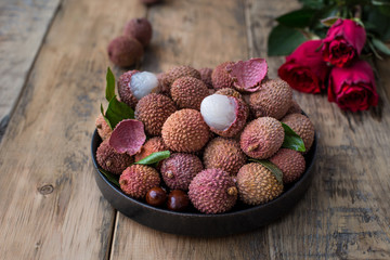 Still life of fresh lychee fruits in a black plate on a wooden background. Rustic style. Decorated with red roses