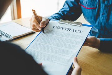 Business people negotiating a contract between two colleagues