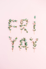 Urban word Friyay. The last day of the work week concept made of eucalyptus branch on white background. Flat lay, top view.