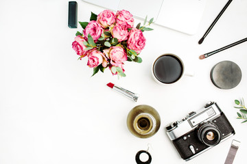 Feminine flat lay, top view workspace with rose flowers bouquet, vintage photo camera, coffee cup and accessories on white background. Women home office concept.