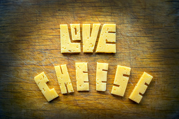 Love Cheese text word on old vintage rustic brown scratched wooden board background. Carve yellow cheddar into letters. Cheese Typography. Food lettering