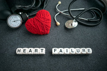 Word HEART FAILURE from white cubes with letters on dark background with red thread heart and tonometer. HEART FAILURE inscription with medical equipment for heart diagnostics, stethoscope