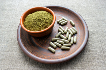 Green capsules and powder on a clay brown plate on a burlap rustic background. Dietary supplements, vitamins and minerals for vegans and vegetarians. Healthy lifestyle, superfood