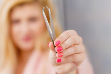 Woman showing tweezers for eyebrows depilating