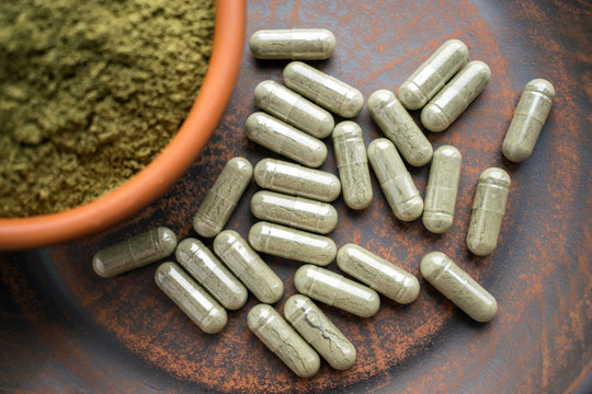 Close up Green capsules and powder on a clay brown plate on a burlap rustic background. Dietary supplements, vitamins and minerals for vegans and vegetarians. Healthy lifestyle, superfood