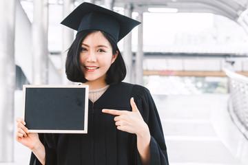 Woman students successful graduation holding empty blank board