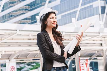 Beautiful woman engineer holding blueprint on city background