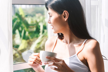 Woman drinking coffee in bedroom in the morning