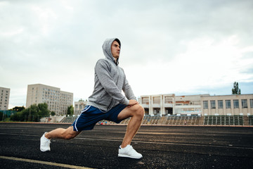 Handsome young sportsman doing lunges, exercises, listening to music, at the stadium.