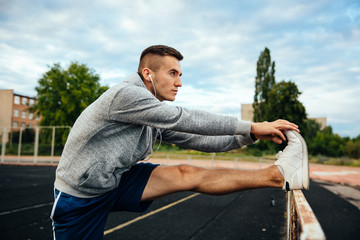 Concentrated young sportsman doing exrcises for legs, listening to music, outdoors Wall mural