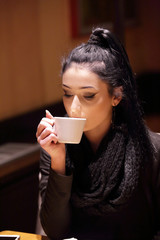 Ragazza sorseggia un caffè seduta al bar