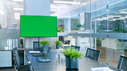 Modern Empty Meeting Room with Big Conference Table with Various Documents and Laptops on it, on the Wall Big TV with Green Chroma Key Screen. Wall mural