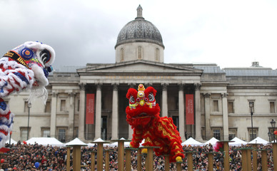 Spectators watch performers dressed in traditional lion and dragon costumes take part in the Chinese New Year parade in front of the National Portrait Gallery in central London