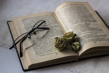 The old book and glasses. Open book, top view. Dry roses.