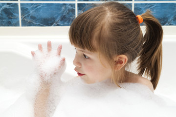 Portrait of pretty little girl in bath. Hygiene concept.