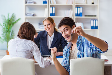 Young family agreeing mortgage contract in the bank for new house