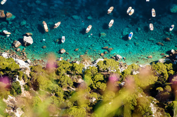 Aerial shot of beautiful blue lagoon at hot summer day with boats sailing around. Top view of people are swimming around the boats.